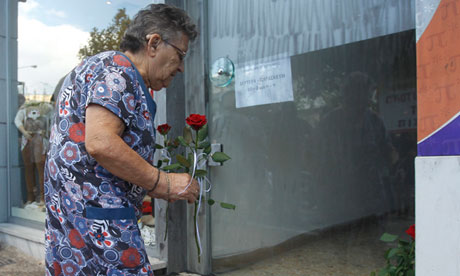A resident of Keratsini, Piraeus, Greece, lays flowers where Pavlos Fyssas was murdered